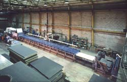 The high-speed continuous production Process Tunnel®, and in the foreground are panels showing both side trimmed and folded edges.